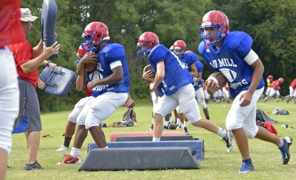 Members of the varsity team run through drills during practice at Old Mill High School on Wednesday afternoon.