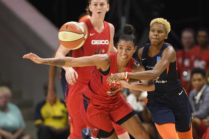 Connecticut Sun guard Courtney Williams, right, battles for the ball against Washington Mystics guard Natasha Cloud, left, in the second half of Game 2 of basketball's WNBA Finals, Tuesday, Oct. 1, 2019, in Washington. The Sun won 99-87. (AP Photo/Nick Wass)