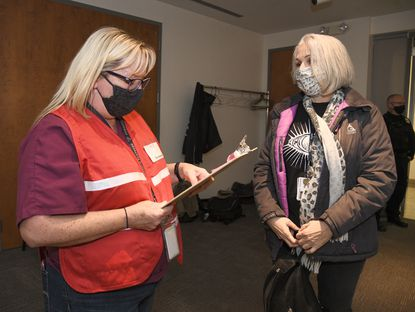Anne Arundel County Health Department screener Carine Davis, left, asks Madonna Gambrell some questions before Gambrell gets her COVID-19 vaccination at a clinic held at the Anne Arundel Community College, Monday, January 18, 2021. (Paul W. Gillespie/Baltimore Sun).