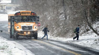 A school bus drops students off at their stop along Sharon Road in Jarrettsville Tuesday afternoon as the snowfall begins to pick up. Schools closed two hours early Tuesday. More snow is forecast Wednesday.