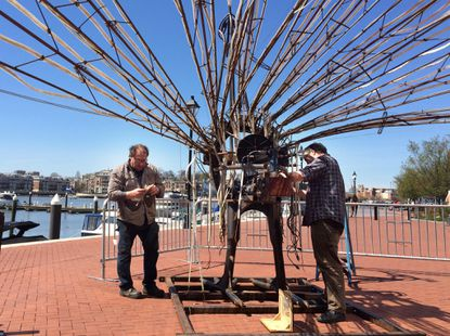 Baltimore artists Tim Scofield, left, and Kyle Miller work to dismantle Charlie, a 12-foot tall peacock, Sunday after the Light City Baltimore festival.