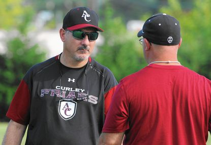 Archbishop Curly football coach Sean Murphy, left, wears Under Armour sunglasses, cap and shirt.