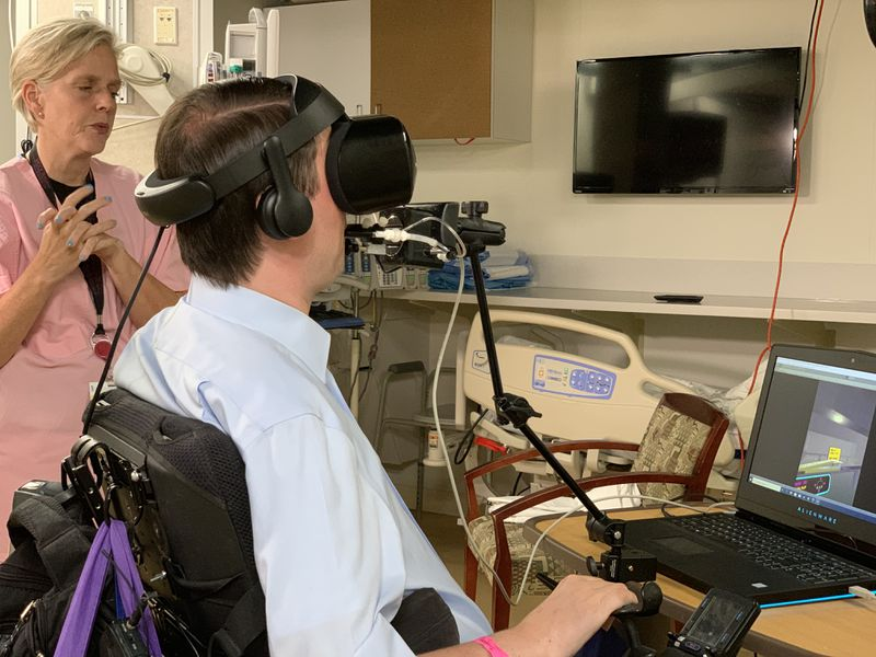 Joshua Basile (seated at computer) tests a virtual reality platform as Dr. Sarah Murthi of Shock Trauma looks on.