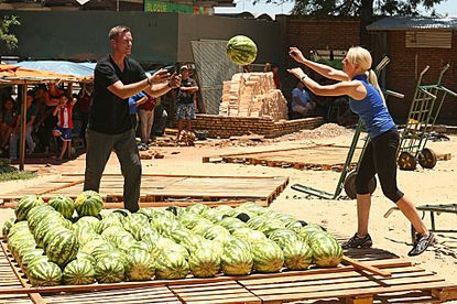 Army couple Dave (left) and Rachel must stack watermelons into a pyramid in order to receive the next clue.