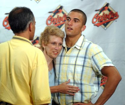Nick Markakis is hugged by his mother, Mary Lou, back when he was introduced as the Orioles' first-round pick in June of 2003.