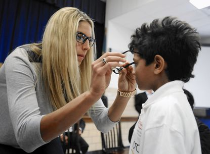 Elena Delle Donne, of WNBA's Chicago Sky, helps fourth-grader Cayleb Reeves try on his new glasses from Vision To Learn.