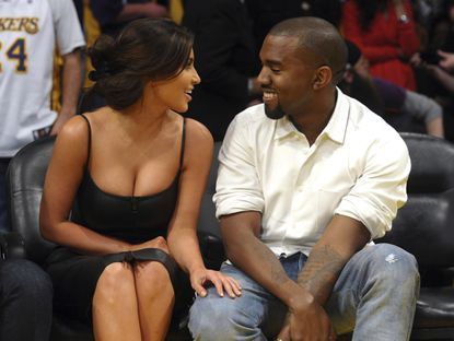 Kim Kardashian and Kanye West talk from their courtside seats before a Los Angeles Lakers game in 2012.