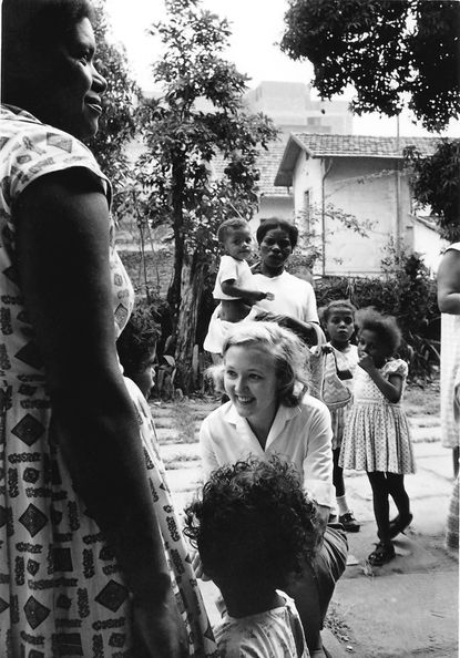 Sally Foster, kneeling, works as a Peace Corps volunteer in the early 1960s in one of the slums of Rio de Janeiro, Brazil. Foster was a health and community development worker.