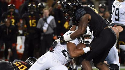 Michigan State's Gerald Holmes, left, is brought down by Maryland's Jesse Aniebonam in the second half of an NCAA college football game, Saturday, Oct. 22, 2016, in College Park, Md. Maryland won 28-17. (AP Photo/Gail Burton)