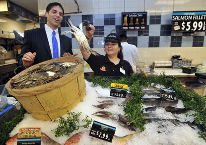 Marshall Klein, chief operating officer of Klein's ShopRite of Maryland, and Stephanie Burns, seafood manager, check out a live crab in the new ShopRite store at Perring Crossing.