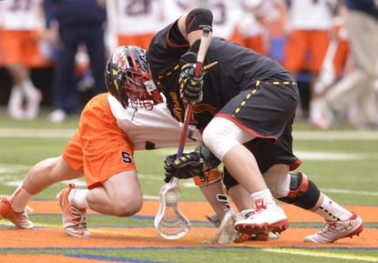 Maryland midfielder Charlie Raffa wins a faceoff during the second quarter of a game against the Syracuse at the Carrier Dome.
