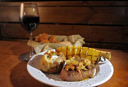 """The eight-ounce filet with crab, baked potato and grilled pineapple wedge, with the """"whatchamacallems"""" appetizer, at Poor Boy Steakhouse."""