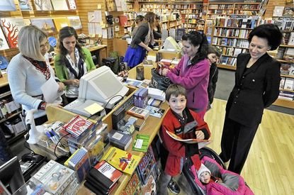 The owner of the Ivy Bookshop, Darielle Linehan (right) watches as Shirley Fergenson (left) and Emma Fesperman ring up a sale for customer Ellada Guchemand. Guchemand was shopping with her children, Alan,front) and Kamran (behind her), and daughter Lily, in baby carrier.