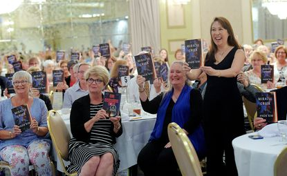 """Author Angie Kim, standing, poses for a photo with the audience as they hold up copies of her novel """"Miracle Creek"""" during the Ninth Annual Day for Book Lovers hosted by the Carroll County Public Library and the Friends of the Carroll County Public Library at Martin's Westminster Monday, Sept. 16, 2019."""
