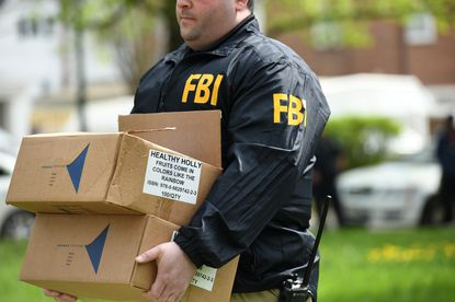 A Baltimore City Council committee will discuss a slate of government reform measures in the wake of the Healthy Holly scandal. In this April 25, 2019, file photo, an FBI agent carries boxes of books from one of then-Mayor Catherine Pugh's homes.