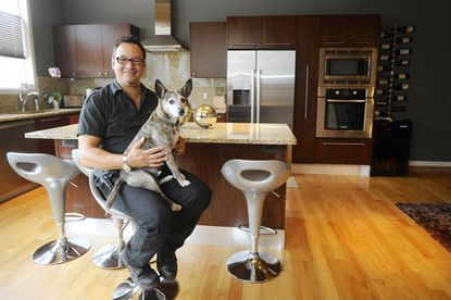 Michael Linnemann and his dog, Stinky, in the kitchen of their dream home at Overlook Clipper Mill.