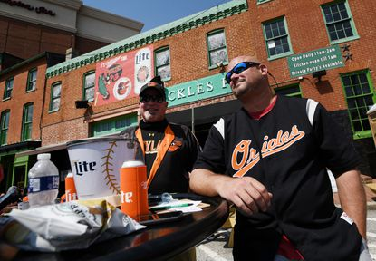 Guy Smith of Westminster, left, and Matt Pisula of Hanover, Pa. sit outside at Pickles Pub before heading into the Baltimore Orioles' home opener at Oriole Park at Camden Yards Thursday, April 8, 2021. Smith and Pisula both work at Maggie's in Westminster and scored tickets to the game from their boss.