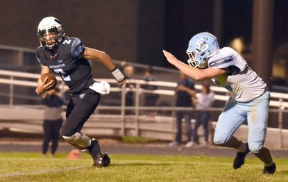 Westminster's Jalen Bradford, left, eludes pressure from South River's Dominic Marick on his way to a second quarter touchdown during a football game at Westminster High School on Friday, September 6.