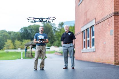 Chet Andes and James Ball fly a drone at Carroll Community College in Westminster.