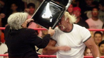 Eric Bischoff, left, president of the WCW, uses a folding chair to smash Hollywood Hulk Hogan in the head after he had attacked wrestler Billy Kidman during the WCW performance in Denver, Monday, April 10, 2000.