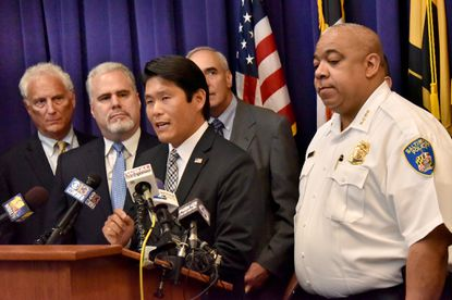 U.S. Attorney Robert K. Hur, at podium, joined Baltimore Police Commissioner Michael Harrison, right, and other officials to announce the launch of the National Public Safety Partnership with the Baltimore Police Department. The three-year PSP program will offer technical and financial support to reduce violent crime. At left is Michael Shatzow, representing the State Attorney's Office, and second from left, Jon Adler, Director of the Bureau of Justice Assistance.