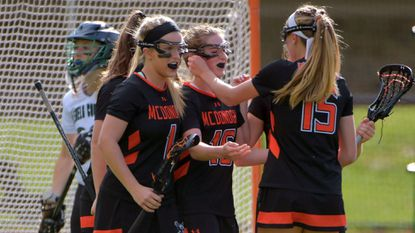 McDonogh's Rachel Anderson (left) and Kayla Abernathy (15) congratulate Izzy Marsh (center) after her goal against the Glenelg Country School Dragons at Dragon Stadium.