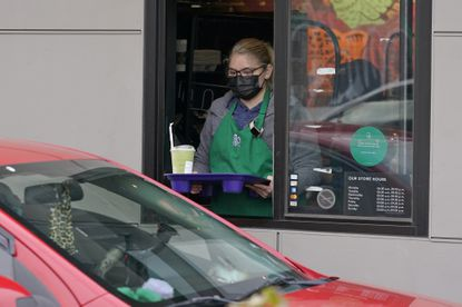 A barista serves up a drink in the drive through lane at a Starbucks Coffee store in south Seattle, Tuesday, Oct. 27, 2020. Starbucks saw faster-than-expected recovery in the U.S. and China in its fiscal fourth quarter. (AP Photo/Ted S. Warren)