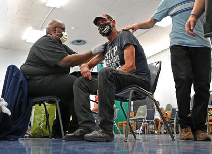 Jovan Crocker, left, a nurse practitioner with MedStar Health, administers a dose of the COVID-19 vaccine to Daniel Boss at the Enoch Pratt Free Library in Baltimore's Brooklyn neighborhood. Boss got his COVID-19 vaccine at the urging of a friend.