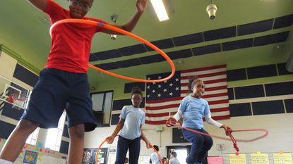 Fourth graders, left to right, Denver Austin, Akira Harper and Symone Browning play during their gym class at the Patterson Park Charter School.