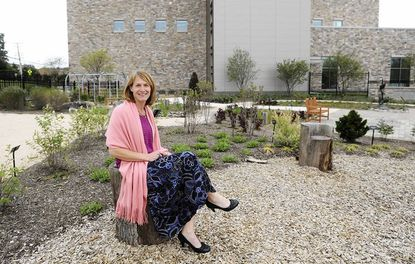 """Rita Hamlet, development specialist for the Howard County Library, sits in the new """"Enchanted Garden"""" at the Miller Branch on Frederick Road."""