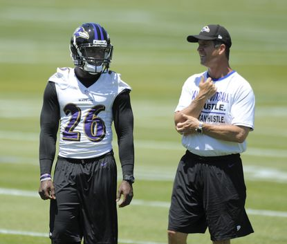 Matt Elam talks to John Harbaugh during a practice.