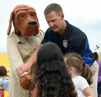 Bel Air Police officer Rick Krause helps McGruff the Crime Dog shake a paw with some new friends during the 2018 National Night Out event at the Aberdeen Target.