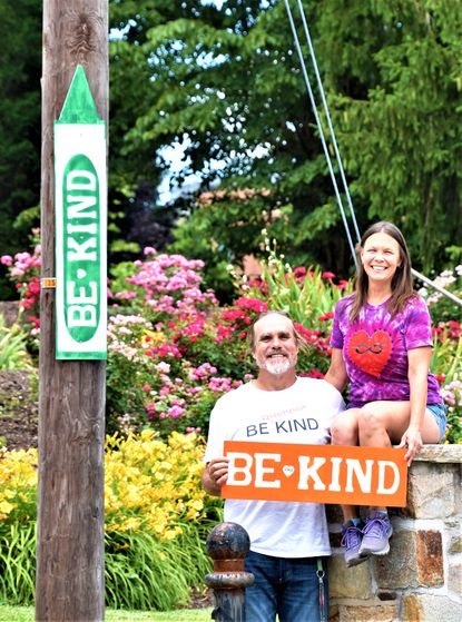 """Eric Hyde Miller and Tina Thomas beside one of their """"Be Kind"""" signs."""