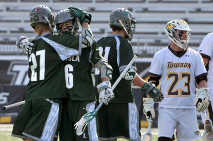 Loyola Maryland's Zach Herreweyers, left, and Brian Sherlock (6) celebrate the Greyhounds' 10th goal in the third quarter as Towson's #23 Tyler Young looks toward the goal. Loyola beat the Tigers, 15-11, at Towson's Johnny Unitas Stadium.