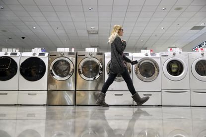 A person passes by LG and Samsung washing machines on display at Abt Electronics in Glenview on Tuesday, January 23, 2018. LG said it will raise prices of its imported washing machines in response to new U.S. tariffs.