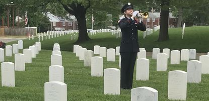 """Bugler Connor Wright plays """"Taps"""" during a Memorial Day service at the historic Baltimore National Cemetery complex. This year's ceremony contained fewer of the traditional trappings than usual to comply with social distancing restrictions put in place during the novel coronavirus pandemic."""