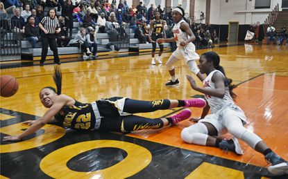 St. Frances' Taneara Moore, left, battles for a loose ball with McDonogh's Treasure Valdez, right, in the third quarter Feb. 6. The Panthers won, 56-46, in a key IAAM basketball game.