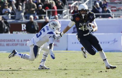 Navy safety George Jamison returns an interception against Middle Tennessee State in the Armed Forces Bowl in Fort Worth, Texas.