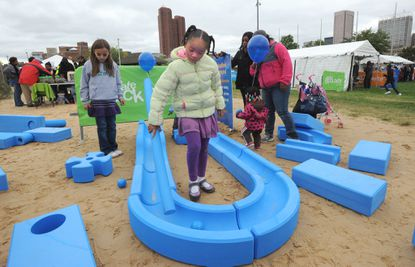 Zawadi Sankofa, 7, center, plays in the Imagination Playground, with her friend Isabel Wu-Karr, 7, at left. They were some of the thousands attending Baltimore's first Ultimate Block Party! at Rash Field.