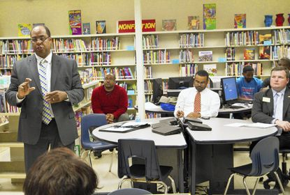 Rainier Harvey speaks to residents during a District 44B candidates' forum at Edmondson Heights Elementary School on May 9 while Charles Sydnor, at center, and Pat Young, right, wait at the table for their turn to speak.