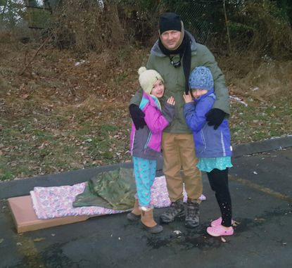 Isabella, left, and Amelia Decker, both now 8 years old, wake up their father, Alexander Decker, in November 2018 after he slept outside to raise money for homeless youths sheltered by the nonprofit Covenant House during the Sleep Out America event.