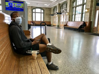Wearing a mask to protect himself because of coronavirus concerns, Elye Bailey gazes at the information board at Pennsylvania Station to check on the status of his train after visiting relatives in Baltimore.