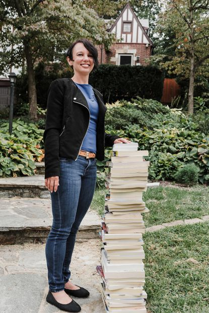 """Anneslie resident Julie Klinger-Luht and a tall stack of phone books headed for """"upcycling,"""" rather than the trash bin. Courtesy Photo / J. Watts Photography"""