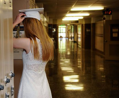 A graduate fixes her cap in the window of a classroom door as she gets ready for Saturday's graduation at the John Carroll School in Bel Air