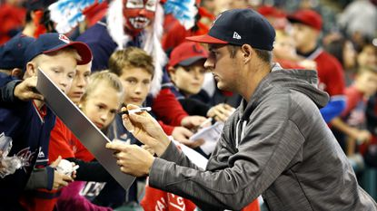 Indians pitcher Trevor Bauer wears a bandage on his right pinkie as he signs autographs before Game 1 of the ALCS in Cleveland.