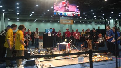 Members of the SC RoboCavs Gold robotics team, in yellow shirts at left, compete in the FIRST Robotics World Championship in Detroit.