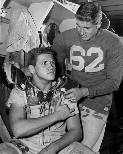 Maryland fullback Ed Modzelewski has his shoulder pads adjusted by teammate Jack Scarbath in 1951.