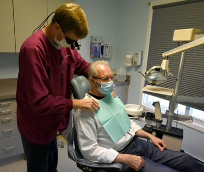 Smile Partners of Havre de Grace dentist Dr. Jim Schall, left, prepares patient Lee Pucklis for a follow up exam during a visit Friday afternoon after some extensive dentistry work performed recently by Schall and his staff.