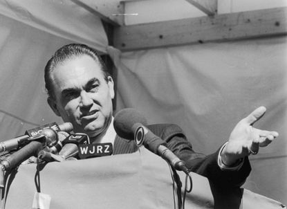 Alabama Gov. and presidential candidate George Wallace, shown answering reporters' questions in Newark, N.J. in 1968, held a rally at Merriweather Post Pavilion on June 27, 1968. **