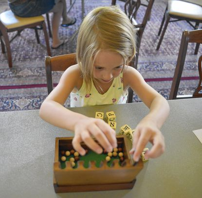 Savannah Wampler, of Pikesville, learns to play an 18th-century game at Montpelier Mansion.